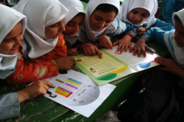 Six Iranian girls looking at educational material