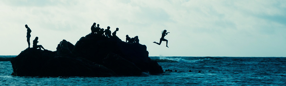 Young woman jumps into water from a cliff. More people on cliff.