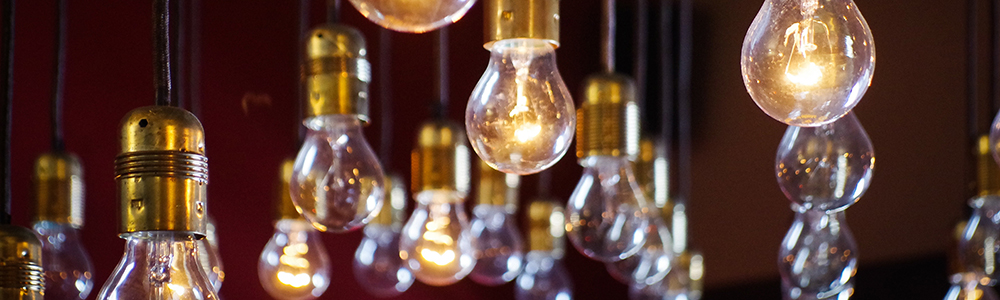 Many hanging light bulbs. Some lit, some not.