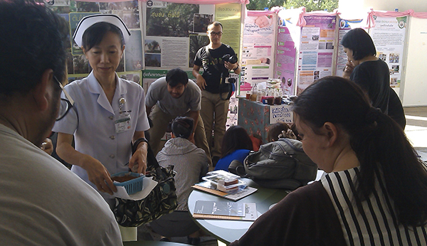 Many people and posters during an exhibition at a hospital
