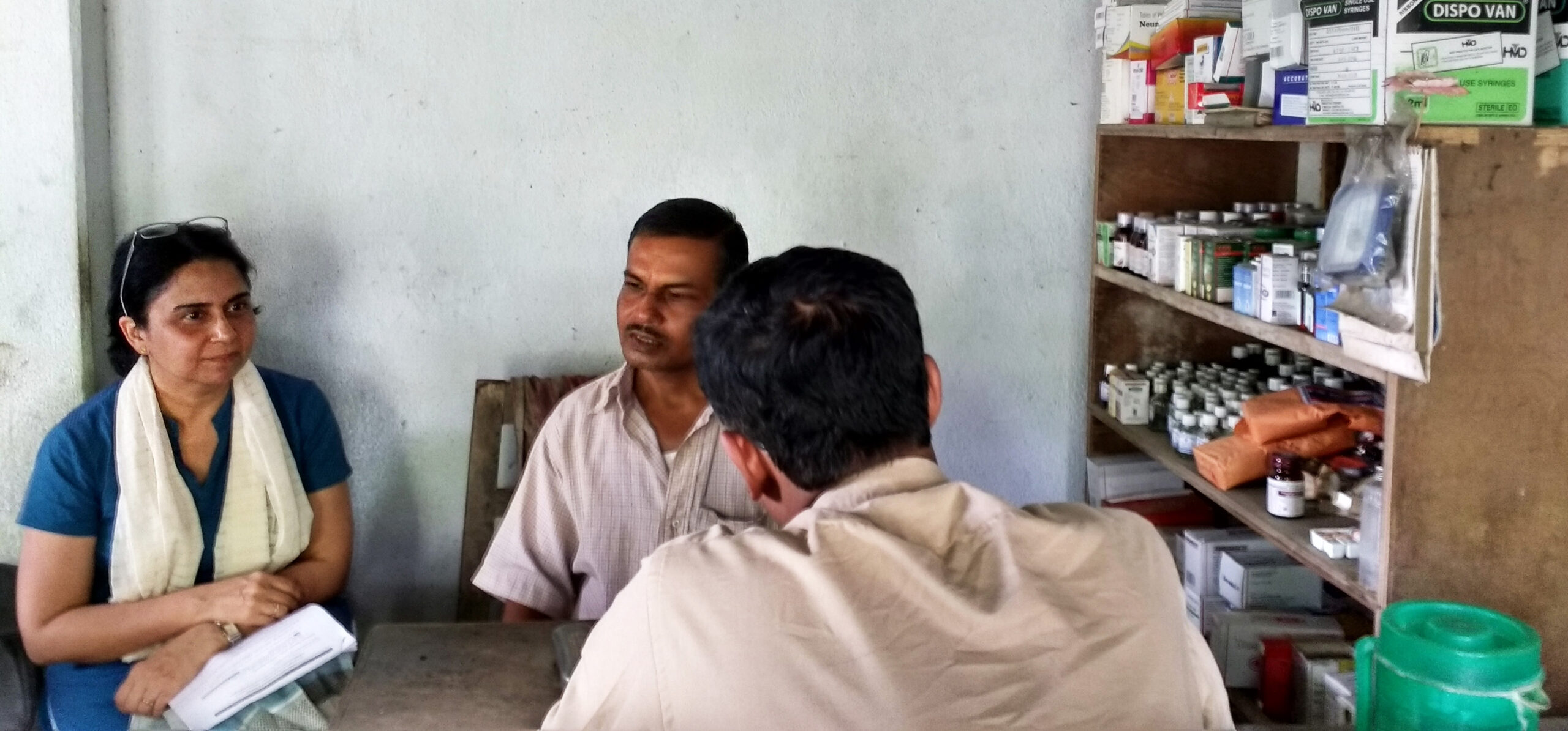 One woman and two men disussing at a health care facility in rural India