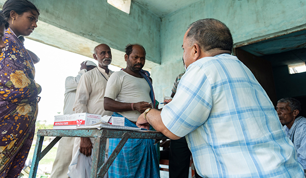 men-standing-in-line-for-medicine-in-rural-are-india