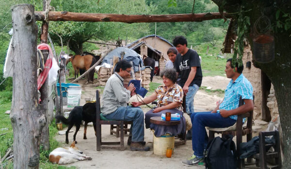 Health care worker Víctor Orellana examining patient outdoors in the small village of San José de Chaquivil. Other patients waiting for their turn.